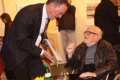 "Mainzer Oberbürgermeister Michael Ebling lässt sich Barbara Petermanns Buch ""Am Anfang war das Holz"" von dem Künstler Reinhold Petermann signieren."